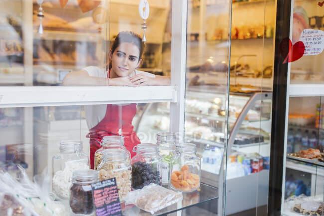 Jeune femme travaillant dans la boulangerie, regardant par la fenêtre — Photo de stock