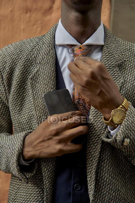 Primer plano de un joven hombre de negocios con estilo arreglando su corbata - foto de stock