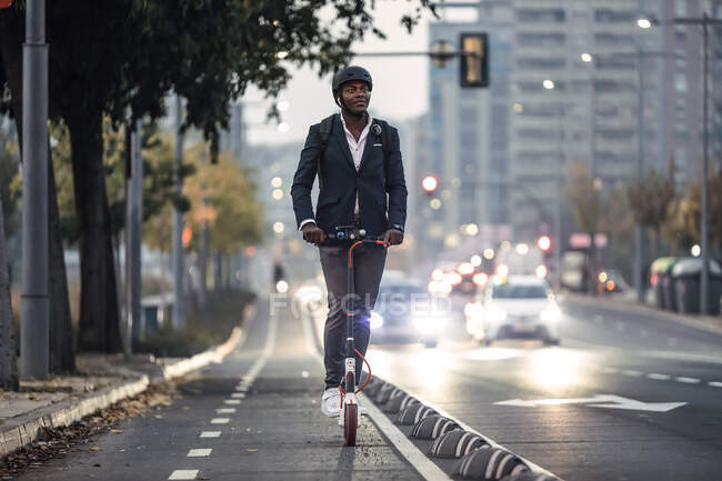 Retrato de hombre de negocios montando vespa de empuje en carril bici en la noche - foto de stock