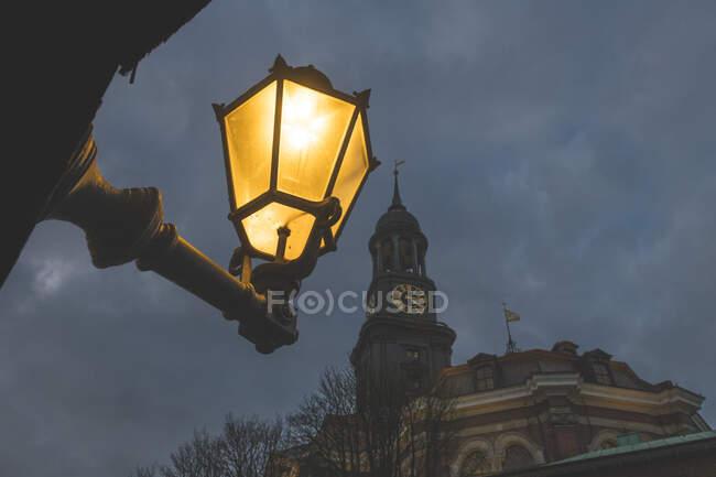 Alemania, Hamburgo, Vista de ángulo bajo de la luz de la calle que brilla contra la torre de la iglesia de San Miguel por la noche - foto de stock