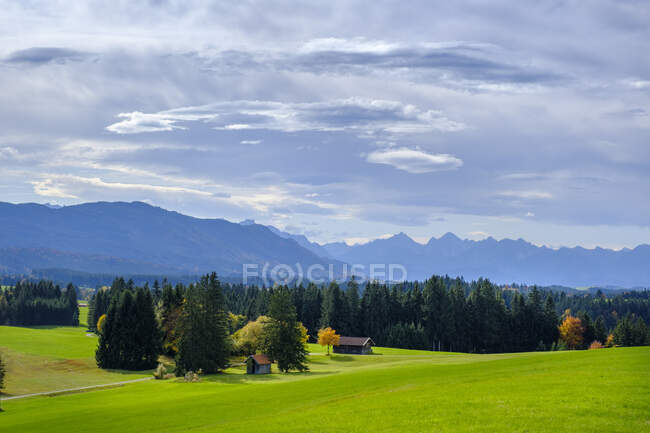Germany, Bavaria, Wildsteig, Clouds over huts standing at edge of alpine forest with Ammergau Alps in background — Stock Photo