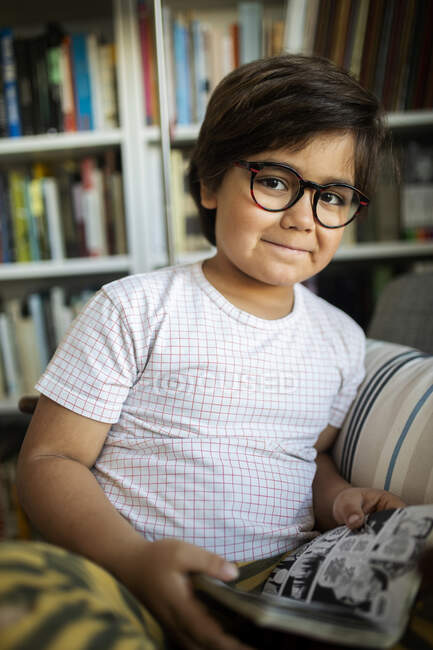 Portrait of smiling boy with glasses reading comic at home — Stock Photo