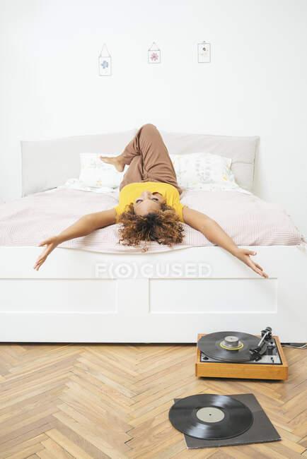 Giovane donna sdraiata sul letto a casa con giradischi sul pavimento — Foto stock