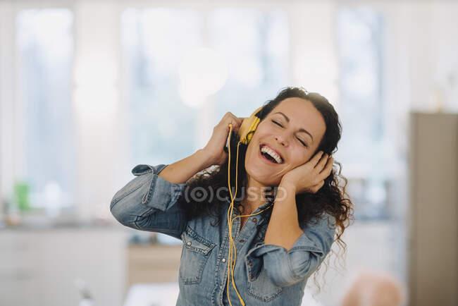 Счастливая женщина слушает музыку, поет и танцует, используя смартфон и наушники — стоковое фото