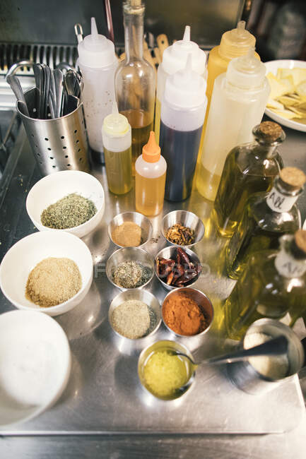 Primer plano de especias y botellas de aceite en la cocina del restaurante - foto de stock