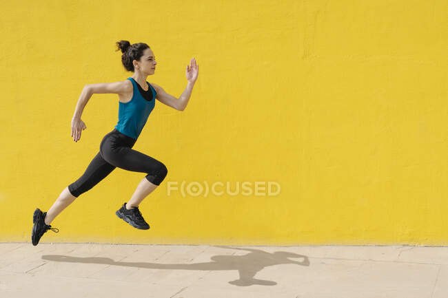 Young woman jogging in front of a yellow wall — Stock Photo
