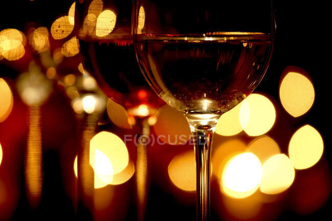 Germany,Glasses of red wine withChristmas lightsin background — Stock Photo