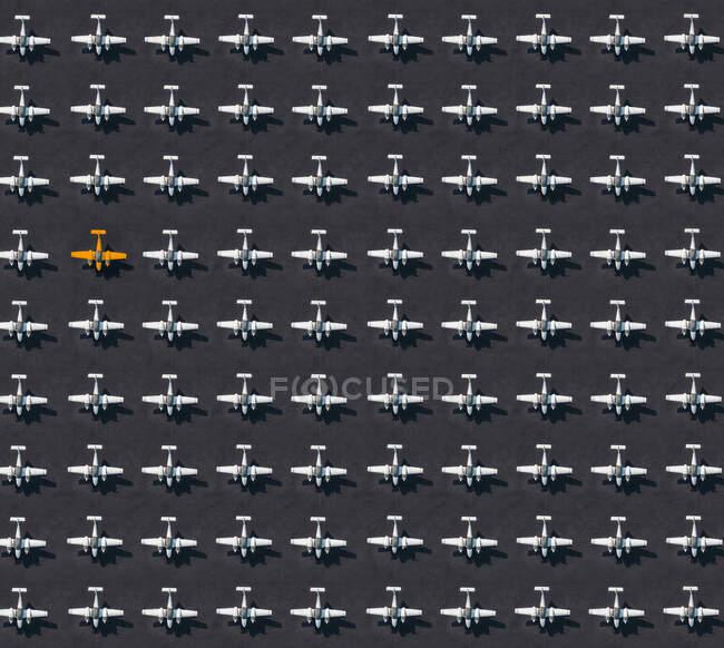 Vista aérea de un solo avión de color naranja rodeado de aviones exclusivamente blancos - foto de stock