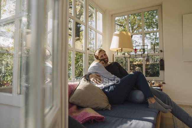 Ласковая пара отдыхает в солнечной комнате дома — стоковое фото