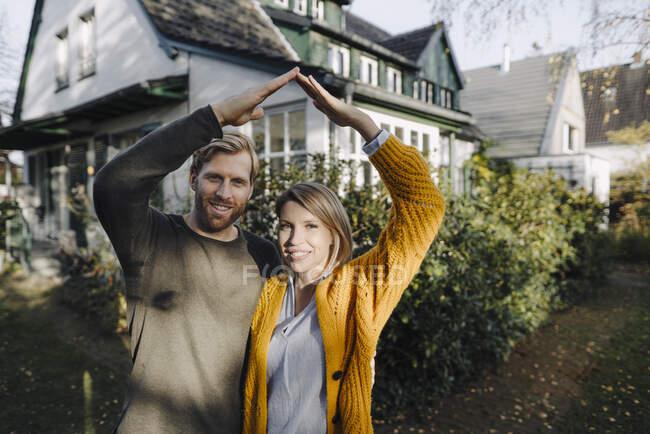 Портрет усміхненої пари, що стоїть перед домом. — стокове фото