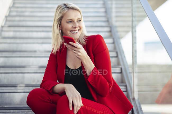 Блакитна ділова жінка у червоному костюмі і без рук телефон, сидячи на сходах. — стокове фото