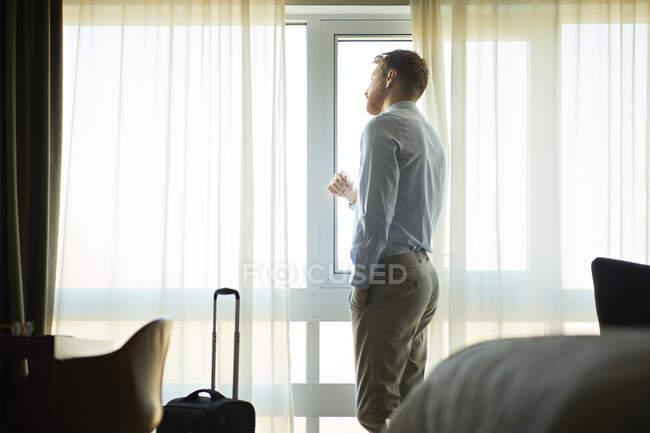 Empresario en habitación de hotel mirando por la ventana - foto de stock
