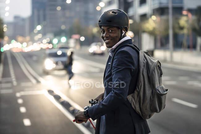 Retrato de hombre de negocios sonriente con scooter push en carril bici por la noche - foto de stock