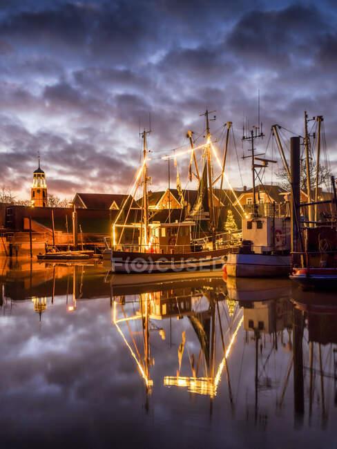 Germany, Lower Saxony, Landkreis Leer, Friesland, Ditzum, Ship illuminated for Christmas at dusk — Stock Photo