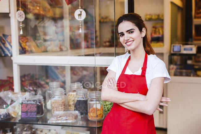 Молодая женщина у входа в пекарню — стоковое фото