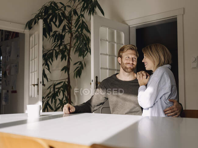 Happy affectionate couple sitting at table at home — Stock Photo