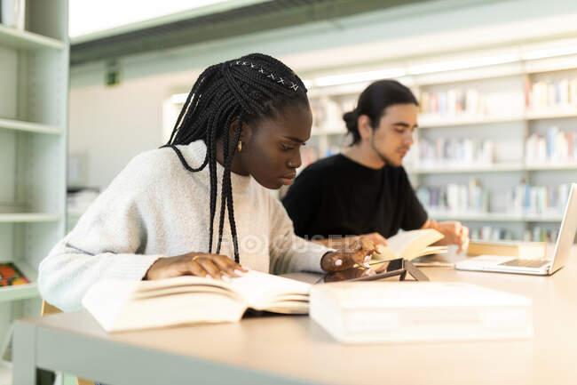 Deux étudiants apprenant dans une bibliothèque — Photo de stock