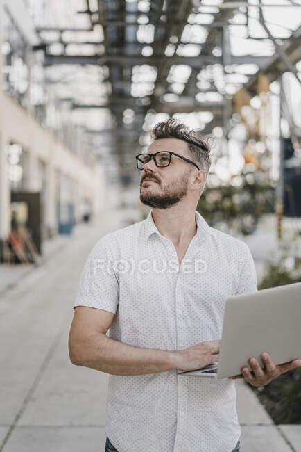 Молодой человек держит ноутбук и смотрит вверх в городе — стоковое фото