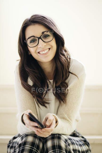 Ritratto di giovane donna sorridente seduta sulle scale con il cellulare in mano — Foto stock