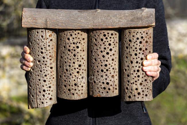 Чоловік тримає дерев'яний готель для бджіл. — стокове фото