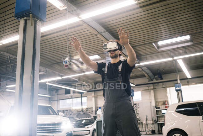 Car mechanic wearing VR glasses in a workshop — Stock Photo