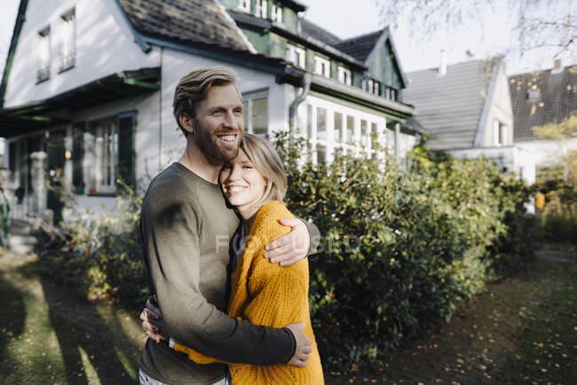 Счастливая пара обнимается перед своим домом — стоковое фото