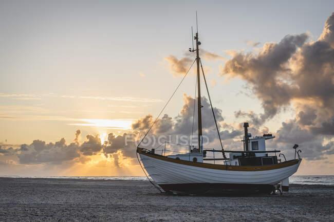 Denmark, Slettestrand, Fishing boat left on sandy coastal beach at sunset — Stock Photo