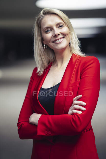 Blond smiling businesswoman with arms crossed wearing red suit and looking at camera — Stock Photo