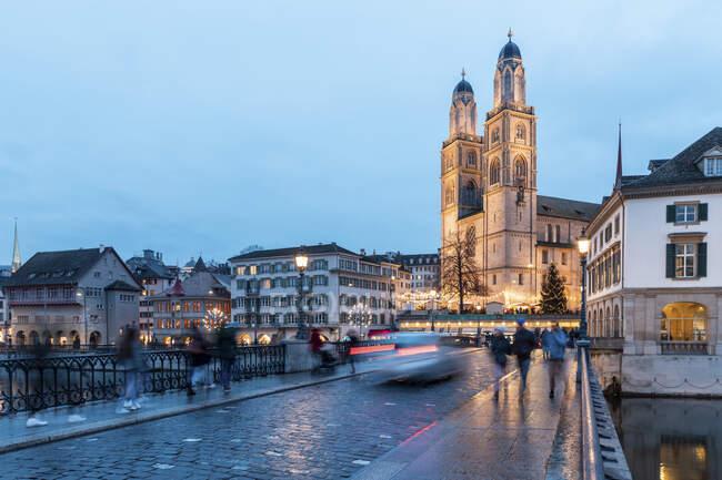 Switzerland, Zurich, Grossmunster church and Munsterbrucke over Limmat river at dusk — Stock Photo