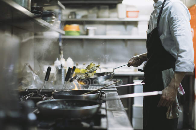 Chef preparing a dish at gas stove in restaurant kitchen — Stock Photo
