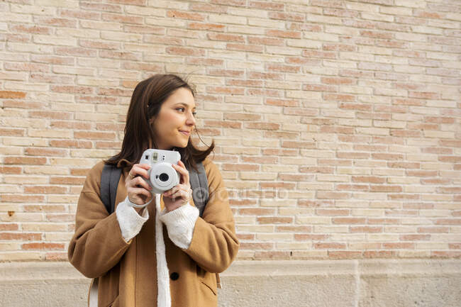 Young woman with camera in front of a brick wall looking around — Stock Photo