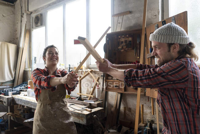 Playful craftswoman and craftsman fighting in their workshop — Stock Photo