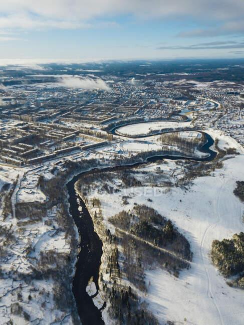 Rusia, Región de Leningrado, Tikhvin, Vista aérea del río Tikhvinka y la ciudad en invierno - foto de stock