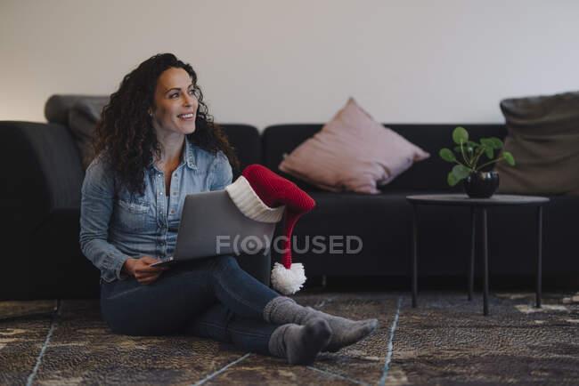 Жінка з Санта-Катом шукає подарунки онлайн, використовуючи ноутбук. — стокове фото