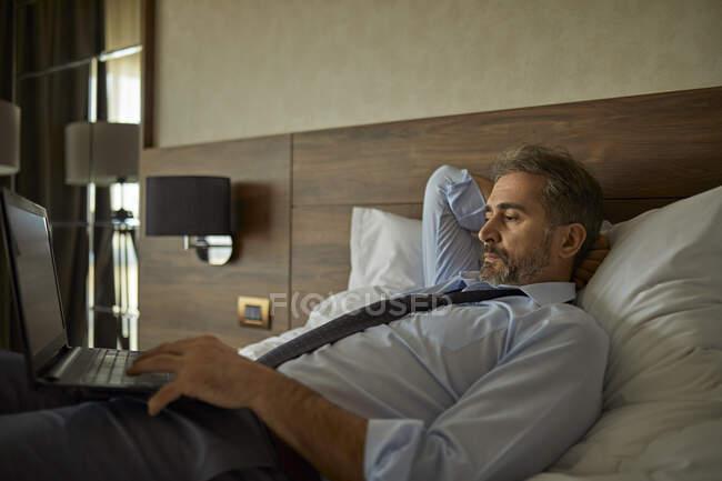Empresario acostado en la cama en la habitación de hotel utilizando el ordenador portátil - foto de stock