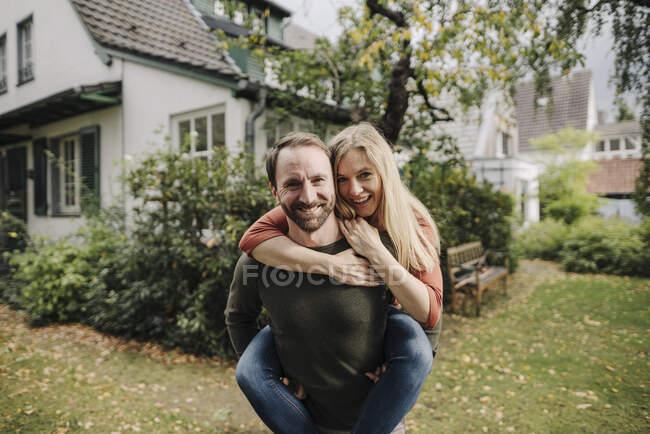 Чоловік, що носить в саду щасливу жінку - голубку. — стокове фото
