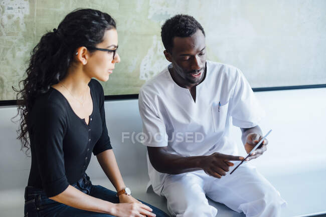 Dentist with tablet speaking with female patient in dental surgery — Stock Photo