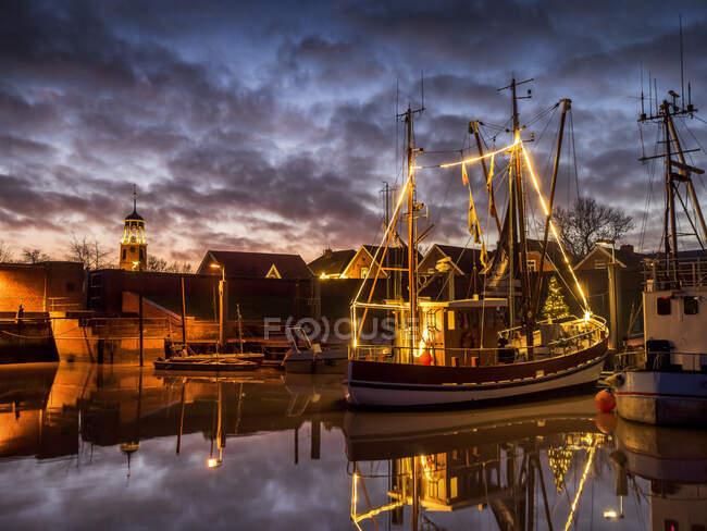 Германия, Нижняя Саксония, Ландкрайс-Лир, Фрисландия, Дитцум, Корабль, освещаемый на Рождество в сумерках — стоковое фото
