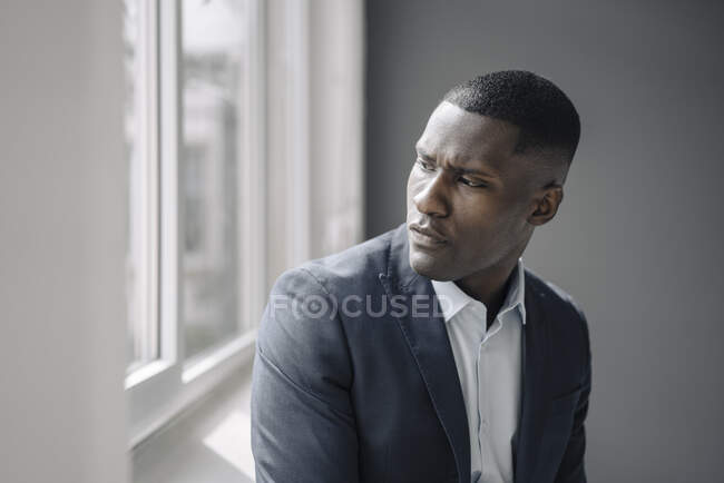 Portrait of serious young businessman looking out of window — Stock Photo