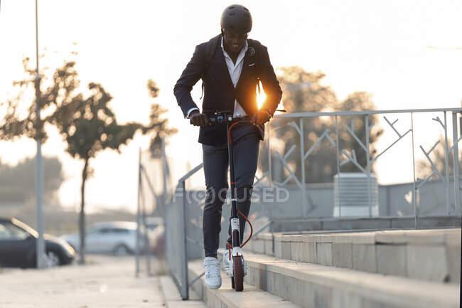 Joven hombre de negocios con mochila y casco de ciclismo a caballo empuje scooter al atardecer - foto de stock