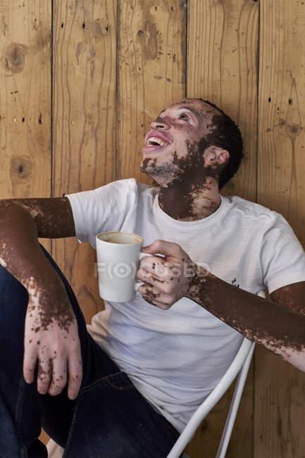 Joven con vitiligo tomando una taza de café y riendo en una cafetería - foto de stock