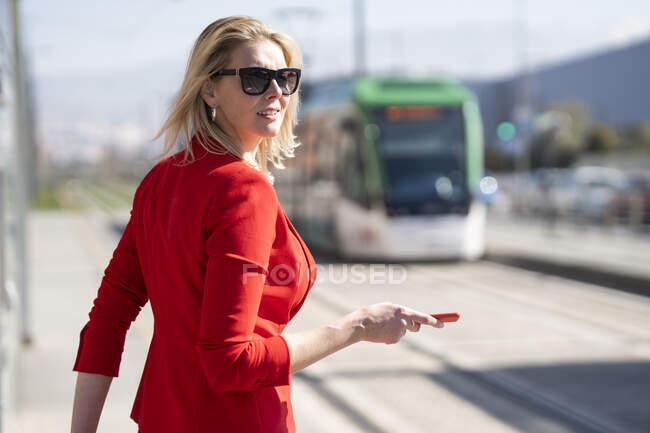 Empresária loira vestindo terno vermelho e esperando o próximo trem — Fotografia de Stock