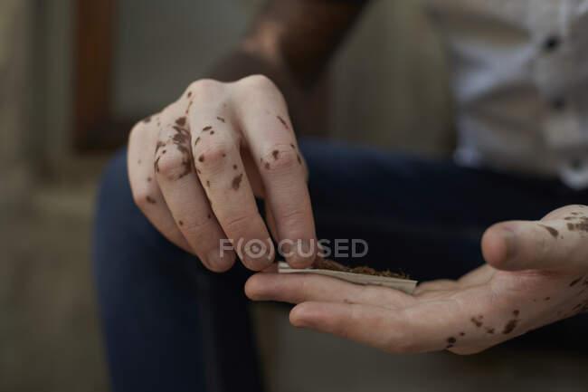 Приблизний план молодого чоловіка з вітиліго прокатки сигарети — стокове фото
