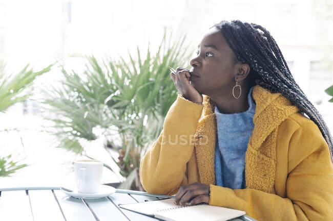 Задумлива молода жінка з запискою в кафе, дивлячись на відстань. — стокове фото