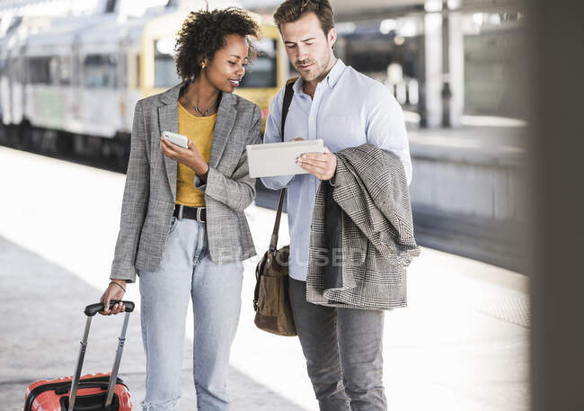 Joven hombre de negocios y mujer de negocios usando tableta juntos en la estación de tren - foto de stock