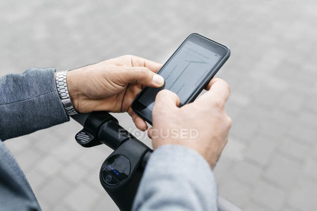Primo piano di uomo d'affari con scooter elettrico utilizzando il telefono cellulare — Foto stock