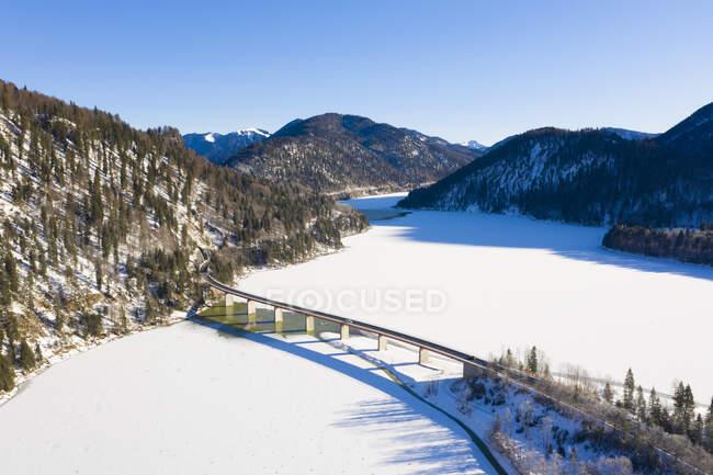 Alemania, Baviera, Lenggries, Drone vista de carretera elevada cruzando el embalse Sylvenstein en invierno - foto de stock