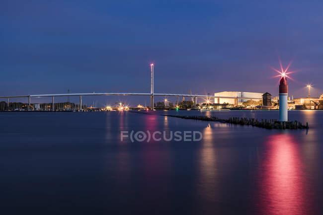 Німеччина, Мекленбург-Західна Померанія, Штральзунд, маяк в кінці пірсу на сутінках з Ругенським мостом на задньому плані. — стокове фото
