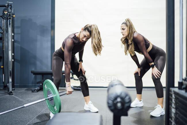 Женщина с сестрой-близнецом упражняется с штангой в тренажерном зале — стоковое фото