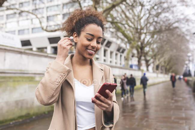 Jovem sorridente com telefone celular e fones de ouvido na cidade, Londres, Reino Unido — Fotografia de Stock